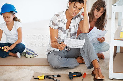 Buy stock photo Mother and daughters sitting together in frustration while trying to build a shelf
