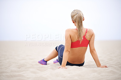 Buy stock photo Rearview shot of a young woman in sportswear sitting on the beach