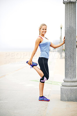 Buy stock photo Portrait of a young woman in sportswear stretching before a run at the beach