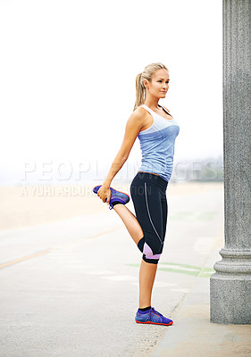 Buy stock photo Shot of a young woman in sportswear stretching before a run at the beach