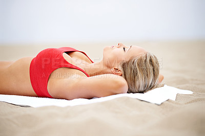 Buy stock photo Shot of a young woman in sportswear lying on the beach
