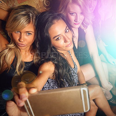 Buy stock photo Shot of a group of young women taking a selfie together in a nightclub