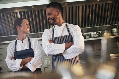 Buy stock photo Cropped shot of professional cooks standing with their arms folded in the kitchen