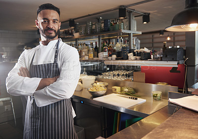 Buy stock photo Cropped portrait of a chef standing with his arms folded in the kitchen