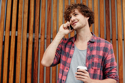 Buy stock photo Cropped shot of a young man using his cellphone while drinking a coffee outside