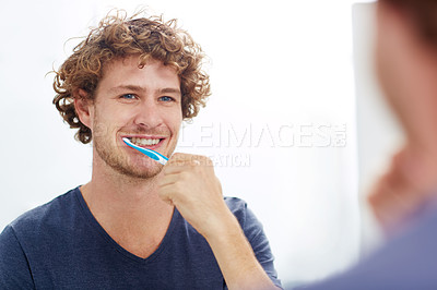 Buy stock photo A young man brushing his teeth in front of the bathroom mirror