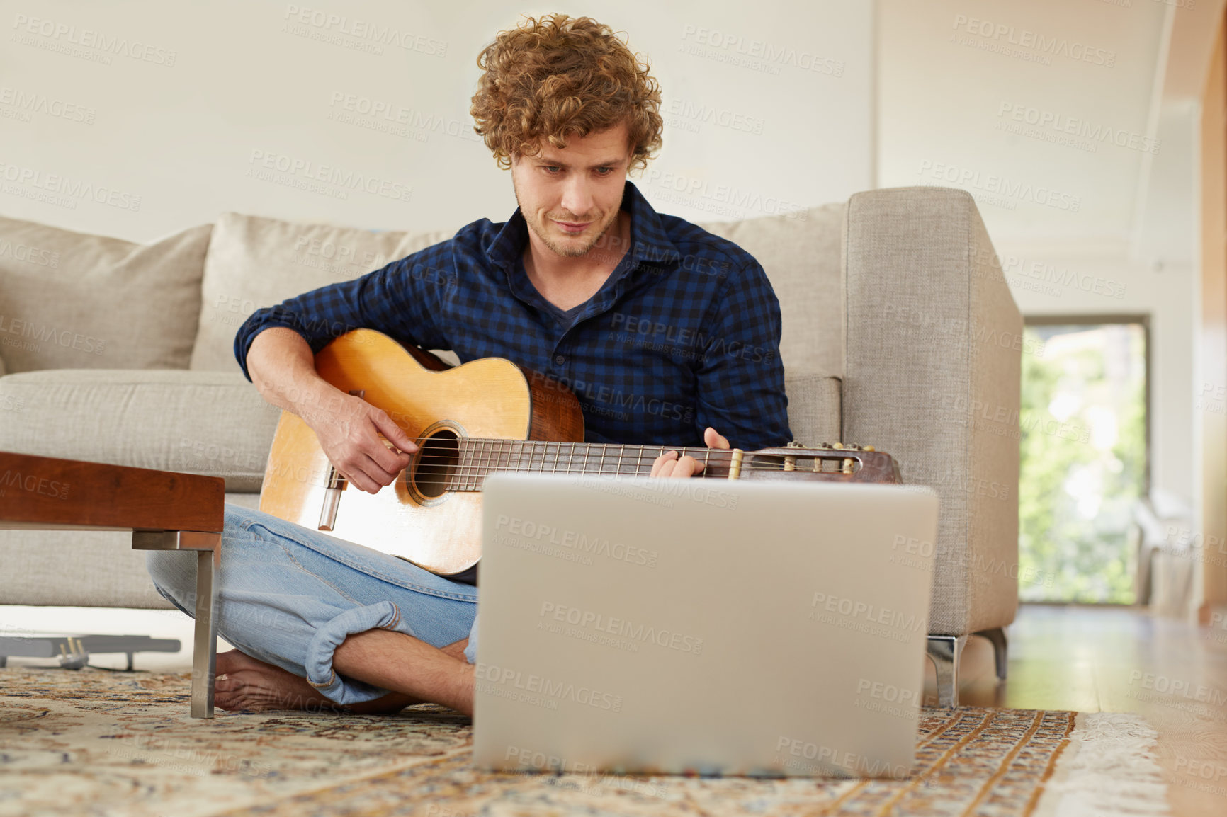 Buy stock photo Shot of a young man playing guitar at home