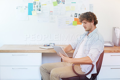 Buy stock photo Shot of a young designer at work on a digital tablet in his home office