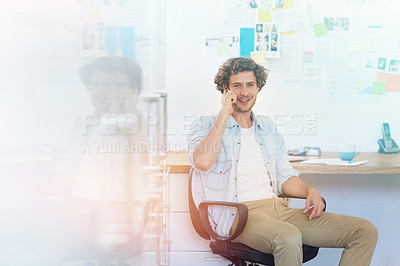 Buy stock photo Portrait of a young designer talking on the phone while working in his home office