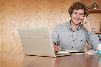 Buy stock photo Cropped portrait of a young businessman making a call while working on his laptop at home