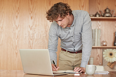 Buy stock photo Cropped shot of a young businessman writing notes while working on his laptop at home