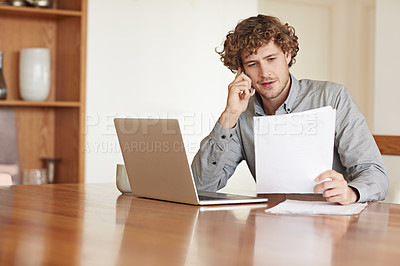 Buy stock photo Cropped shot of a young businessman making a call while working on his laptop at home