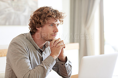 Buy stock photo Cropped shot of a young businessman looking thoughtful working on his laptop at home