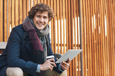Buy stock photo Cropped portrait of a young man drinking coffee and using his tablet while sitting on a bench outside