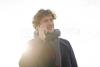 Buy stock photo Cropped shot of a young man using his cellphone outdoors
