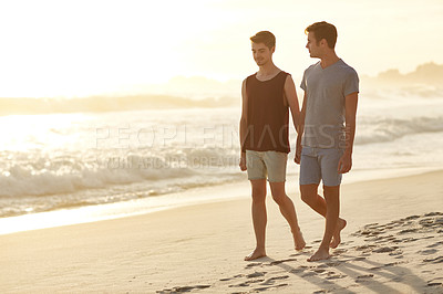 Buy stock photo Shot of a young couple walking along the beach