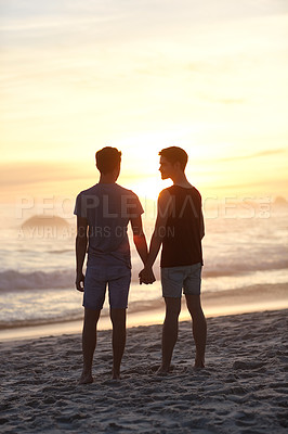Buy stock photo Rearview shot of a couple standing on the beach at sunset