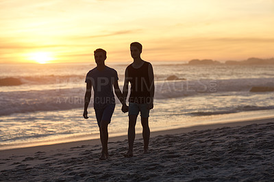 Buy stock photo Shot of a young couple walking along the beach at sunset
