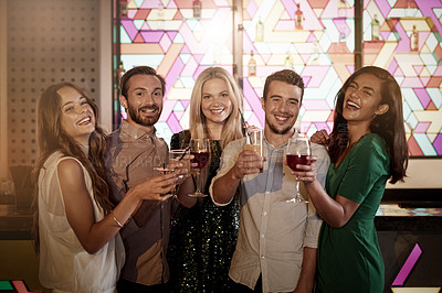 Buy stock photo Portrait of a group of friends holding their drinks while standing together in a bar