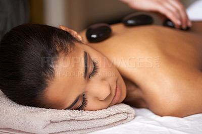 Buy stock photo A young woman receiving a hot stone massage at a spa
