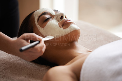 Buy stock photo Cropped shot of a young woman receiving a facial treatment at a spa
