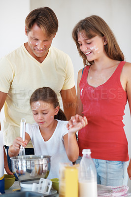 Buy stock photo Family preparing food in the kitchen with young girl whisking flour