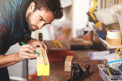 Buy stock photo Cropped shot of a carpenter making measurements on a plank of wood