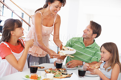 Buy stock photo Family sitting at table having breakfast with woman serving pizza