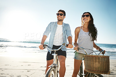 Buy stock photo Cropped shot of a young couple cycling on the beach