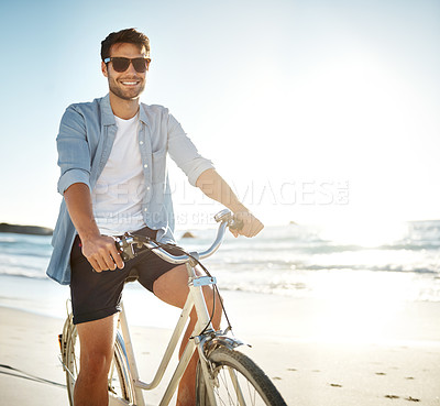 Buy stock photo Cropped shot of a young man cycling on the beach
