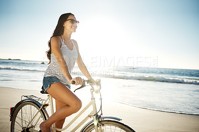 Buy stock photo Cropped shot of a young woman cycling on the beach