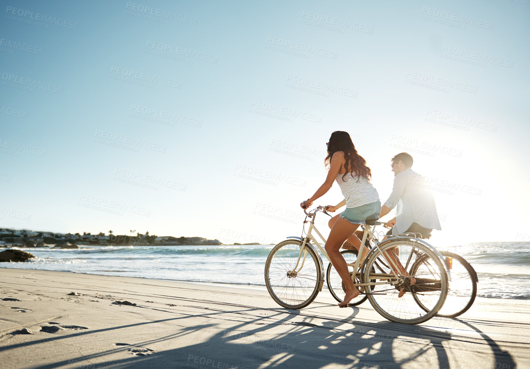 Buy stock photo Full length shot of a young couple cycling on the beach