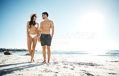 Buy stock photo Shot of a young couple enjoying a day at the beach
