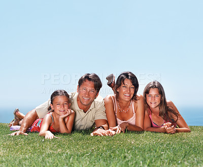 Buy stock photo Portrait of happy family lying together on grass and smiling - copyspace