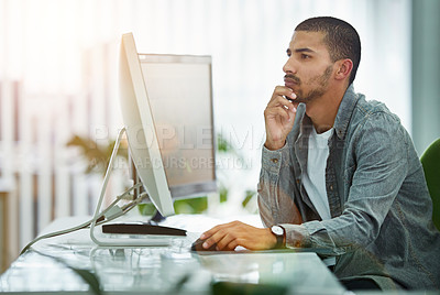 Buy stock photo Shot of a young designer working at his computer in an office