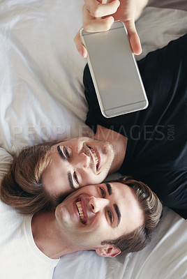 Buy stock photo Shot of a young couple taking a selfie while lying on their bed