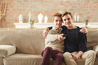 Buy stock photo Shot of a happy young couple watching tv together at home