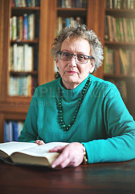 Buy stock photo Portrait of a senior woman sitting at a table reading