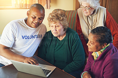Buy stock photo Shot of a volunteer showing a group of senior women how to use a laptop