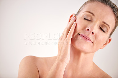 Buy stock photo Cropped studio shot of an attractive mature woman touching her skin