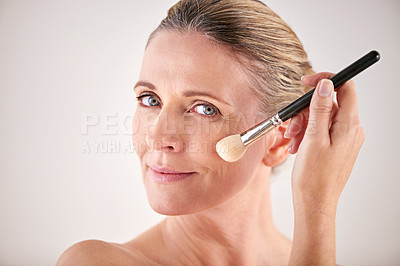 Buy stock photo Cropped studio shot of an attractive mature woman applying makeup with a brush