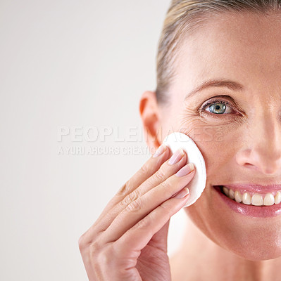 Buy stock photo Cropped studio shot of a mature woman cleansing her face with a cotton pad