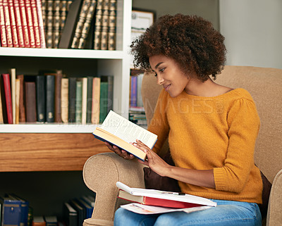 Buy stock photo Cropped shot of a young woman studying on her sofa