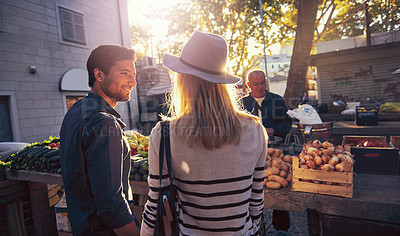 Buy stock photo Shot of a young couple standing by a vegetable market stall in a foreign city