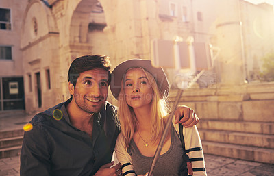 Buy stock photo Shot of a young couple taking a selfie with a selfie stick while touring through an old city