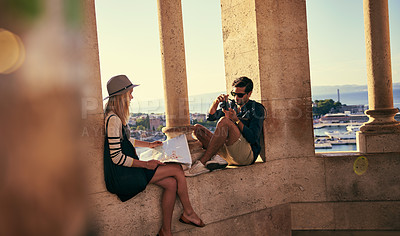 Buy stock photo Shot of a couple looking at a map while touring a foreign city