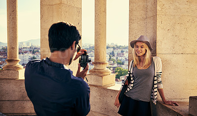 Buy stock photo Shot of a young man taking a picture of his girlfriend while touring a foreign city