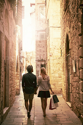 Buy stock photo Rearview shot of a young couple working through a foreign city