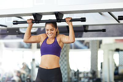 Buy stock photo Cropped shot of a young woman doing pull ups in the gym