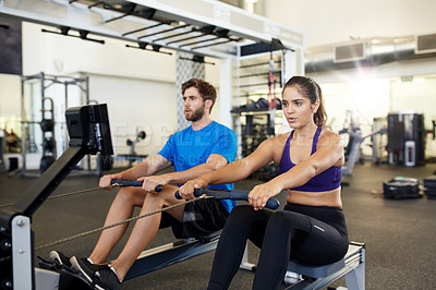 Buy stock photo Shot of two young people using the rowing machines in the gym